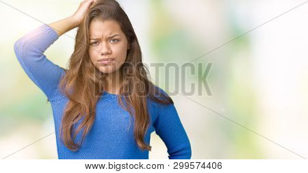 Young beautiful brunette woman wearing blue sweater over isolated background confuse and wonder about question. Uncertain with doubt, thinking with hand on head. Pensive concept.