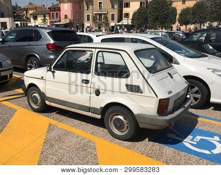 Peschiera, Italy - April 21, 2019: White Fiat 126 Parken On A Public Handicapt Parking Lot.
