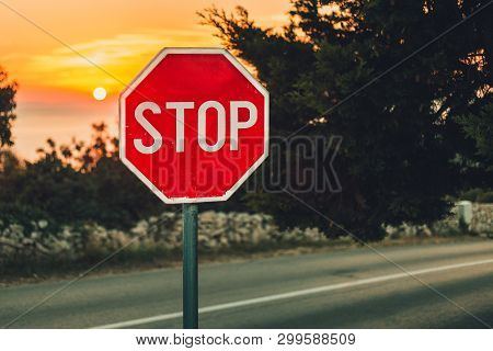 A Traffic Sign Stop In Coastline With Road  And Sea On Background - Photo On Sunset. Illuminated Sig
