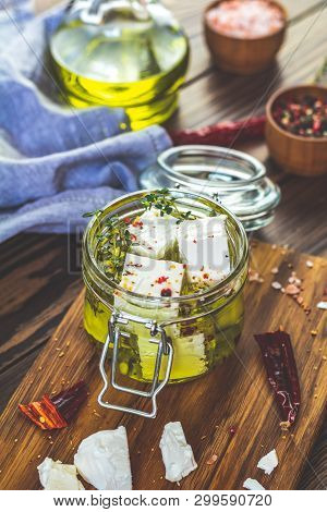 Feta Cheese Marinated In Olive Oil With Fresh Herbs In Glass Jar. Wooden Background