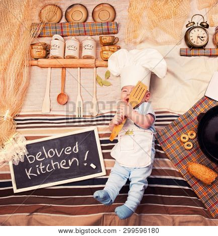 Happy smiling infant cook baby boy portrait wearing apron and chef hat posing against textile decoration of a kitchen interior