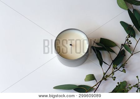 Eucalyptus Branches With Leaves Next To A Soy Wax Candle On White Background