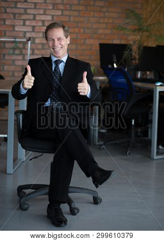 Businessman In Dark Suit Sitting On Chair And Having Thumbs Up. Glad After Signing Agreement. Busine