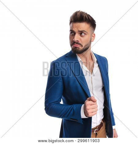 goofy man in suit looking away with hand on lounge jacket on white background