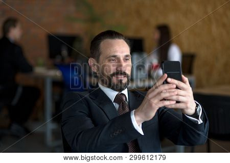 Happy Businessman Sitting At Table And Making Selfie On Smartphone In Office. Relaxing During Lunch