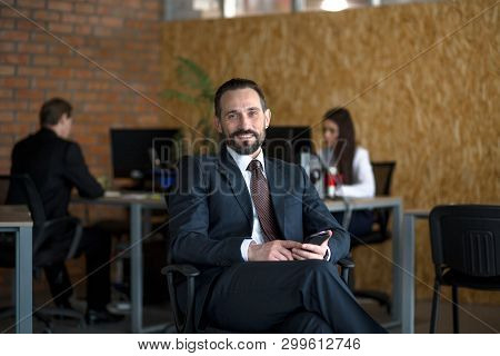 Handsome Businessman Sitting On Chair In Office. Wearing Suit. Colleagues On Background. Business Co