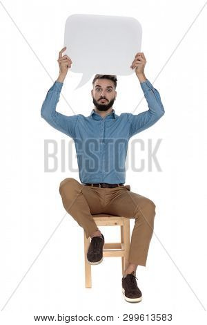 goofy man in blue jeans shirt sitting with an empty message bubble up in the air on white background