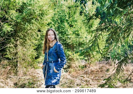 Beautiful Young Girl With Long Blond Hair In A Blue Denim Jacket In A Green Forest On A Sunny Spring