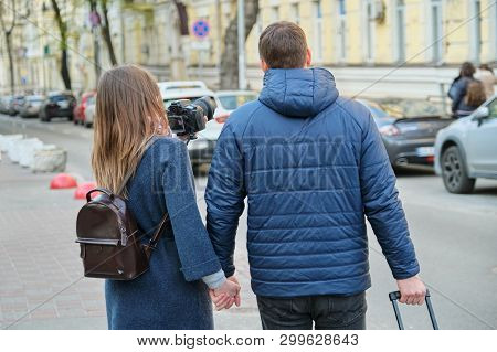 Tourists Young Couple Walking Around The City With Camera Suitcase, View From The Back, Youth Travel