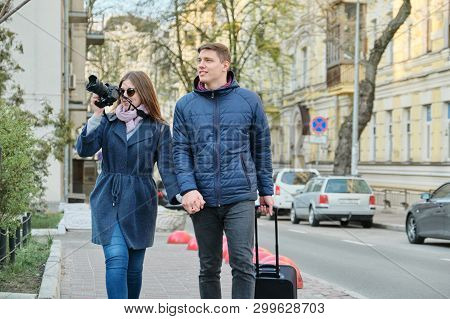 Young Positive Couple Of Young Men And Women Blogger In City With Camera. Travel, City Blogging.