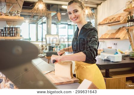 Shop clerk woman in deli cutting cheese