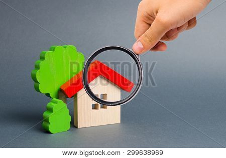 Magnifying Glass Is Looking At A Wooden House And Trees. Environmentally Friendly And Environmentall