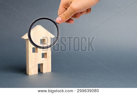 Magnifying Glass Is Looking At A Multi-storey Building Residential House On A Gray Background. Mortg
