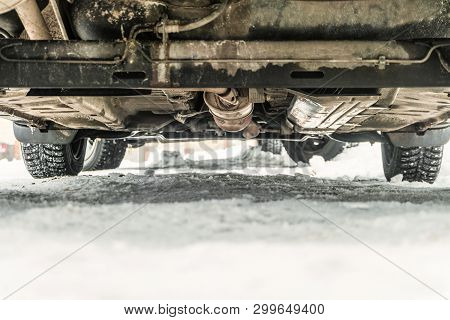 Bottom of the car with studded tires on a winter snowy road. Road clearance. Chassis close-up with limited depth of field. poster
