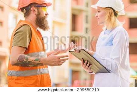 Safety Inspector Concept. Woman Inspector And Bearded Brutal Builder Discuss Construction Progress.