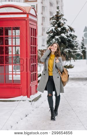 Full-length Portrait Of Cheerful Stylish Lady Talking On Phone While Walking Around Winter City. Out