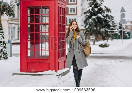 Amazing Young Woman In Gray Coat Talking On Phone On The Street With Green Spruce On Background. Out