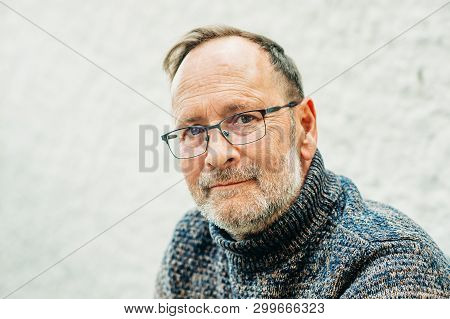 Outdoor Portrait Of 50 Year Old Man Wearing Brown Pullover And Eyeglasses