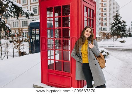 Ecstatic Woman In Trendy Yellow Sweater Posing With Pleasure Next To Red Phone Booth In Winter. Outd