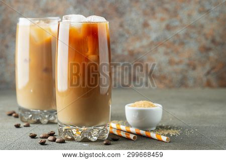 Ice Coffee In A Tall Glass With Cream Poured Over And Coffee Beans. Cold Summer Drink On A Brown Rus