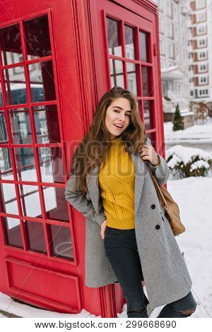 Inspired Female Model In Gray Coat Standing Beside Call-box In December Day With Gently Smile. Outdo