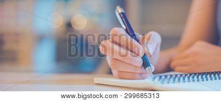 Woman Hand Is Writing On A Notepad With A Pen In Office.web Banner.