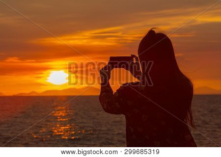 The Silhouette Of A Girl Shooting A Sunset At The Beach.