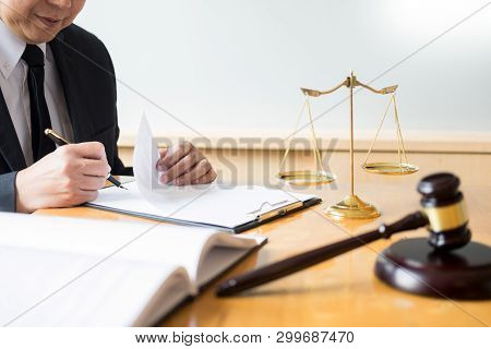 Male Lawyer Working With Contract Papers And Reading Law Book In A Courtroom, Justice And Law Concep