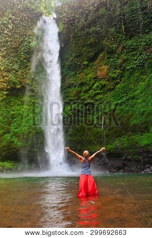 Young Woman Travel In Bali Rainforest. Happy Girl Enjoy Jungle Nature. Stand In Natural Pool Under W