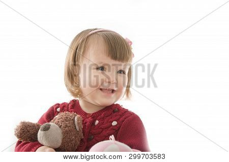 Little Girl Smiling Happy. Cute Caucasian Baby With Bear And Doll Isolated On White Background