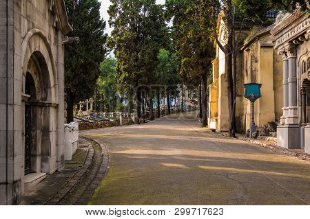 Perspective view of the curved footpath with graves and crypts on the Montjuic Cemetery in sunny day, Barcelona, Catalonia, Spain poster