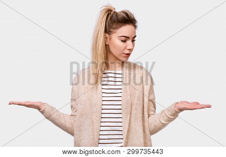 Portrait Of Puzzled Blonde Pretty Young Woman Shrug Shoulders, Looks Uncertain, Confused And Looking