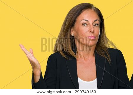 Beautiful middle age business adult woman over isolated background clueless and confused expression with arms and hands raised. Doubt concept.