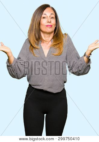 Beautiful middle age business woman clueless and confused expression with arms and hands raised. Doubt concept.