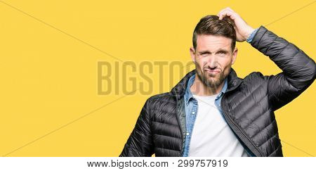 Handsome man wearing winter coat confuse and wonder about question. Uncertain with doubt, thinking with hand on head. Pensive concept.