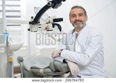 Mature Stomatologist Posing On Workplace, Near Dental Microscope, Leaning On Dentist Chair. Handsome