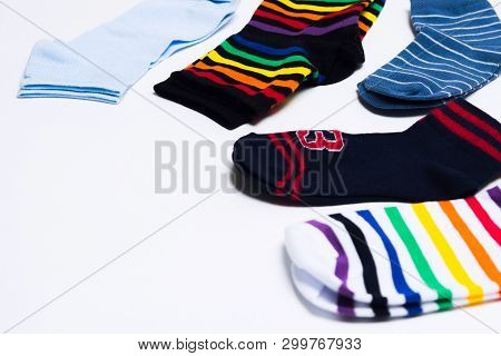 Different Colorful Textile Clothes For Legs, Socks On White Background With Copy Space. Selective Fo