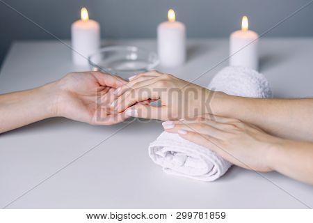 Manicurist hands doing massage to female clients hands. Woman hand receiving manicure procedure. Spa salon. Beautiful woman hands having nail treatment procedure. poster
