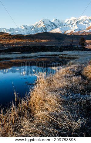 Reflection Of Snowy Mountain Ridge In Lake. Autumn In Mountains. Travel Altai.