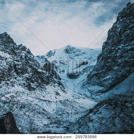 Severe Mountain Peaks Under Snow. Dark Atmosphere Of Nature.