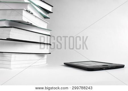Reading Books With An E-book. Concept Of Education. Stack Of Books And E-book On White Background