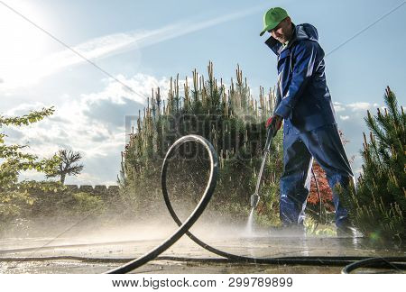 Garden Washing Maintenance. Caucasian Worker In His 30s With Pressure Washer Cleaning Brick Paths.
