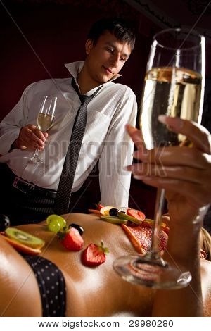 Man and naked woman decorated  by fruits with glass of champagne