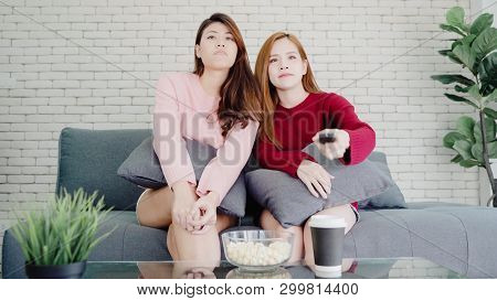Lesbian Asian Couple Watching Tv Laugh And Eating Popcorn In Living Room At Home, Sweet Couple Enjoy