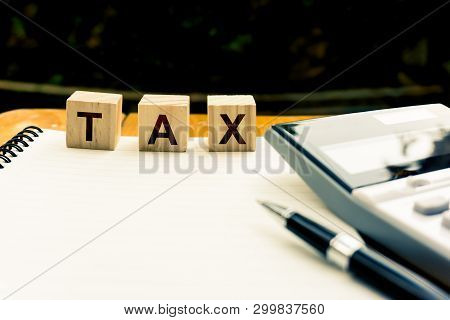 Taxation And Annual Tax Concept. A Wooden Block With Message On Blank Note Book, Calculator And Blac