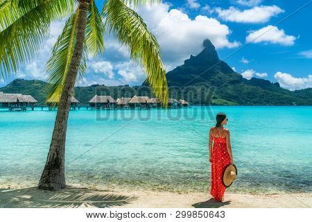 Bora Bora luxury hotel vacation tourist woman relaxing by ocean beach with view of Mt Otemanu in Tahiti, Frenc Polynesia. High End resort with overwater bungalows villas.
