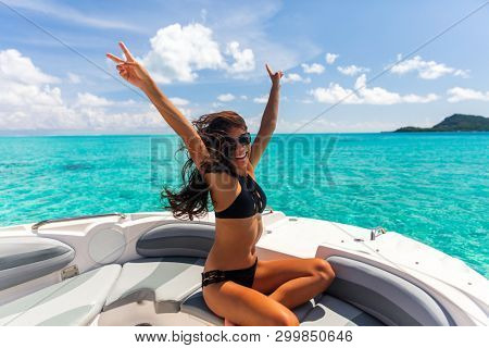 Luxury yacht party woman enjoying freedom having fun with arms up in the wind on high end boat summer vacation trip. Laughing young Asian woman in elegant black bikini, long hair and sun tanned body.
