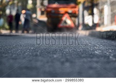Blurred Background, Repair Roads. Road Construction. New, Just Laid Asphalt, Leaves From A Tree On T