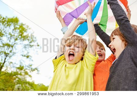 Three boys as winners in a ball game are happy and cheering with enthusiasm