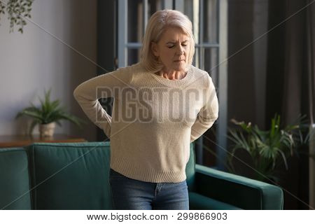 Unhappy Grey Haired Mature Woman Touching Back, Suffering From Backache